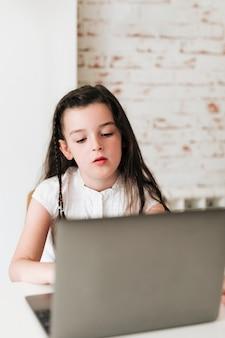 Chica de tiro medio mirando la computadora portátil