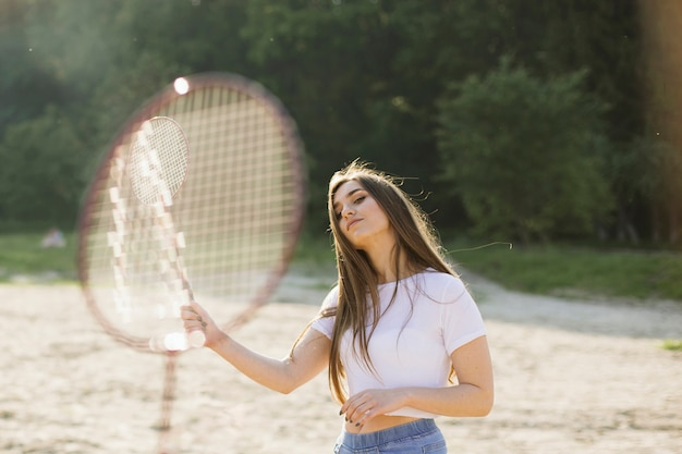 Chica de tiro medio con raqueta de badminton