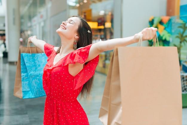 Chica de tiro medio sintiéndose alegre en el centro comercial.