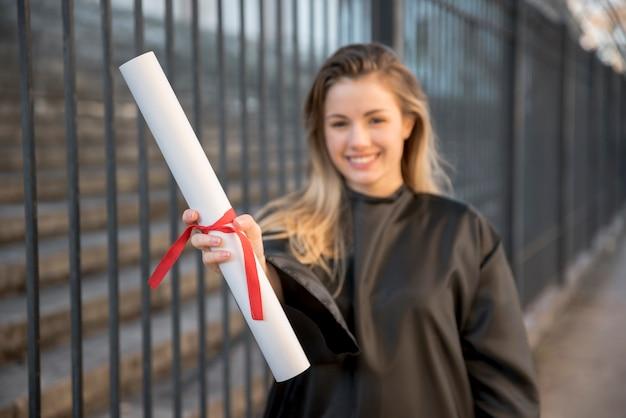 Chica de tiro medio sonriendo sosteniendo su certificado