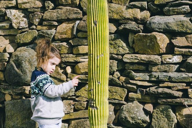 Chica tocando cactus