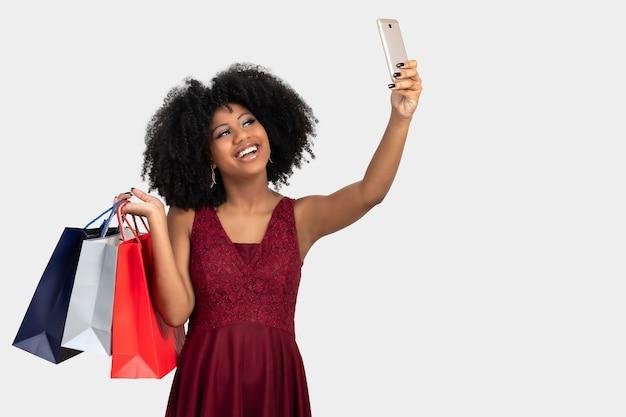 Chica toma autorretrato con teléfono celular mientras sostiene bolsas de la compra.