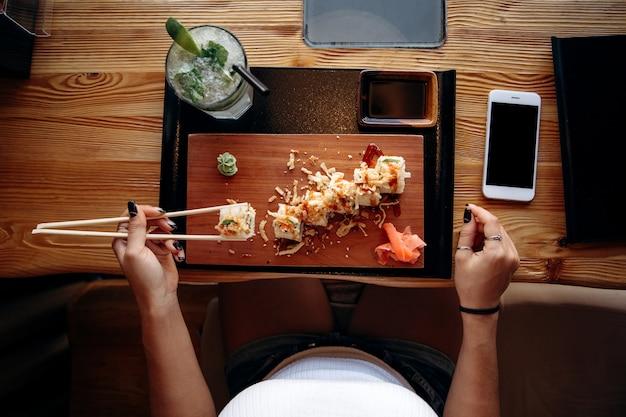 Chica toma sushi en el restaurante japonés. vista desde arriba.