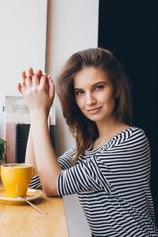 Chica tomando café en una cafetería.