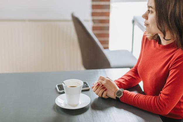 Chica tomando café en un restaurante