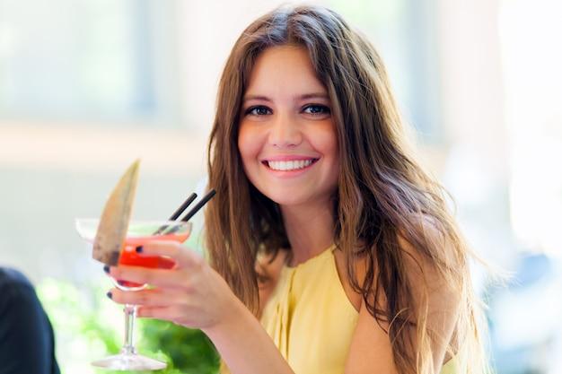 Chica tomando un cóctel en un pub