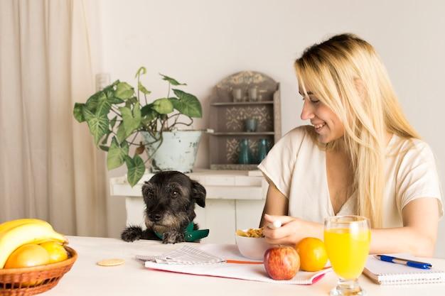 Chica tomando desayuno saludable con perro