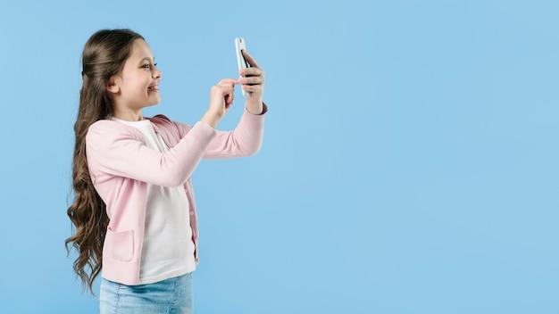 Chica tomando una foto con el teléfono en el estudio