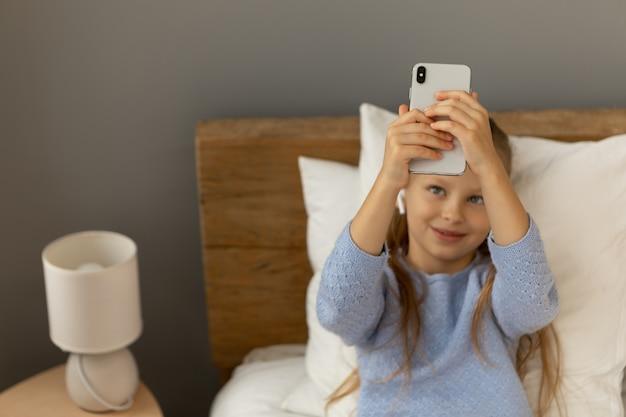 Chica tomando un selfie mientras está acostada en la cama