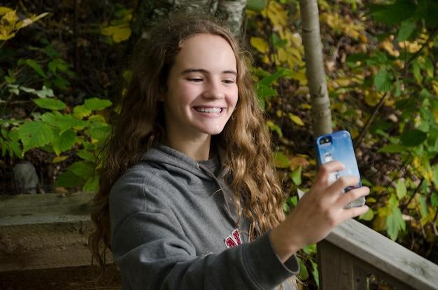 Chica tomando selfie con un teléfono inteligente, lago de los bosques, ontario, canadá