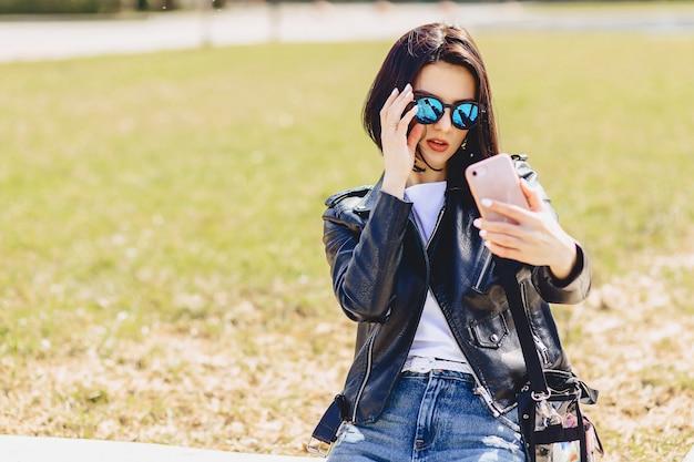 Chica tomando selfie en el teléfono y sonriendo