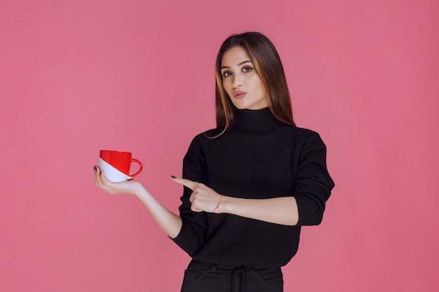 Chica tomando una taza de café en la pausa para el café.
