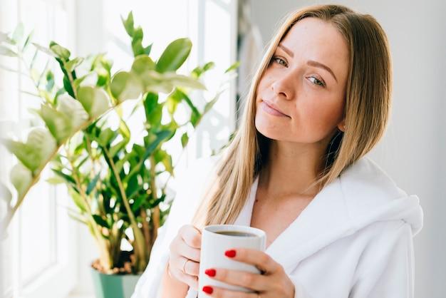 Chica tomándose un café en el baño