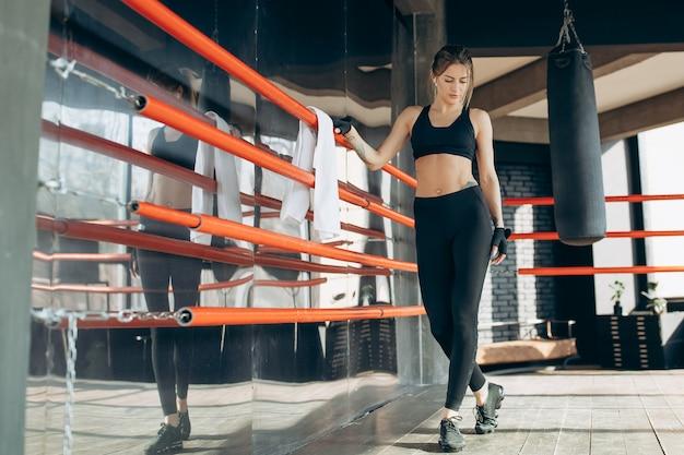 Chica en top de moda y polainas posando en el pasillo. modelo de fitness con una hermosa figura deportiva para anunciar ropa y una dieta saludable