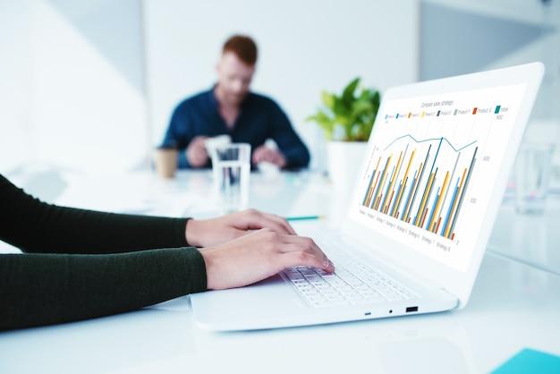 Chica trabaja en una computadora portátil con el concepto de estadísticas de la empresa de interconexión y uso compartido de internet
