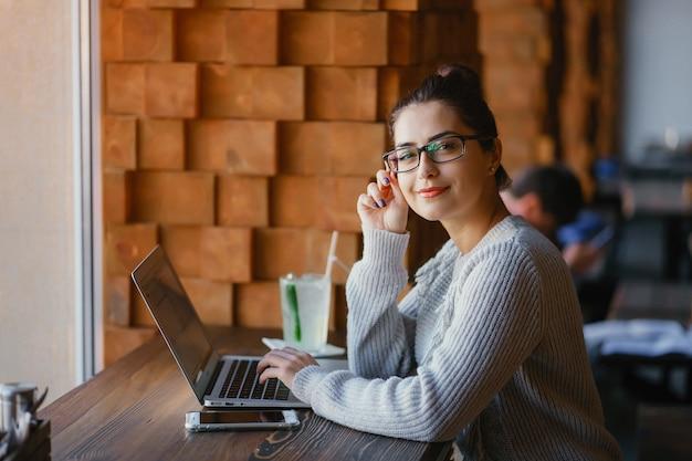 Chica trabajando en una computadora portátil en un restaurante