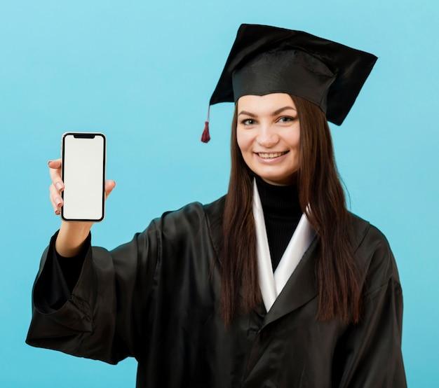 Chica en traje académico con teléfono