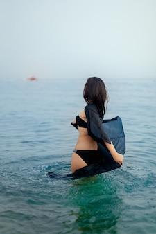 Chica en traje de baño y una capa negra bailando en el agua, el mar, la playa, la vista trasera, el estilo de vida,