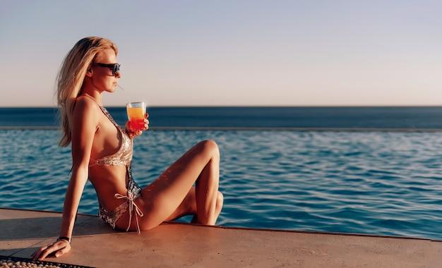 Chica en un traje de baño caro con un cóctel en sus manos pasa sus vacaciones cerca de la piscina en el resort