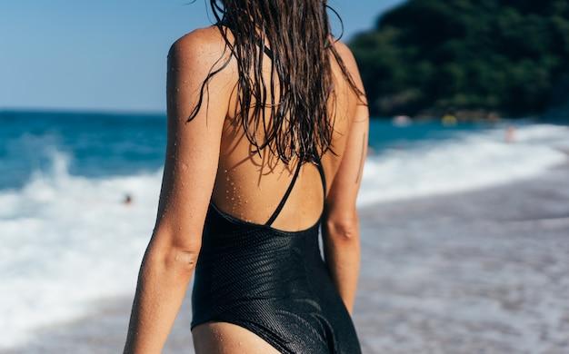 La chica en traje de baño negro junto al mar. vista trasera.