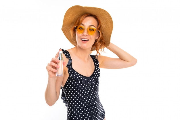Chica en traje de baño retro aplica bloqueador solar sobre un fondo blanco.