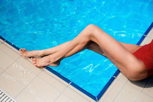 Chica en traje de baño rojo en piscina azul