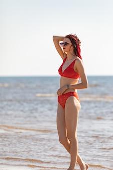 Chica en traje de baño rojo en la playa