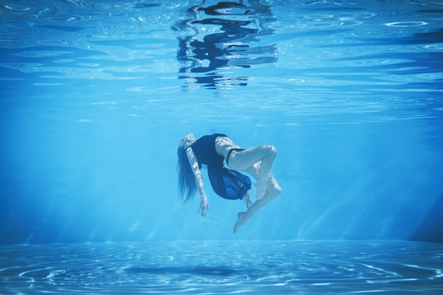 Chica en traje de baño y túnica se acuesta en el agua de la piscina