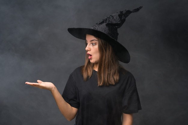 Chica con traje de bruja para fiestas de halloween sobre pared oscura aislada con copyspace imaginario en la palma