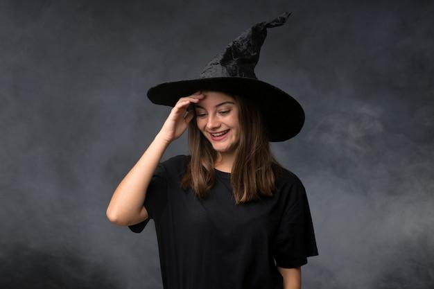 Chica con traje de bruja para fiestas de halloween sobre pared oscura aislada riendo