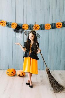 Chica en traje de bruja con magia de escoba