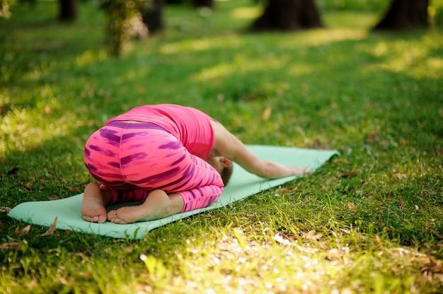 Chica en traje deportivo rosa practicando yoga en el parque en pose de niño