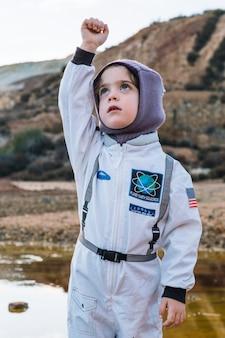 Chica en traje espacial con la mano arriba