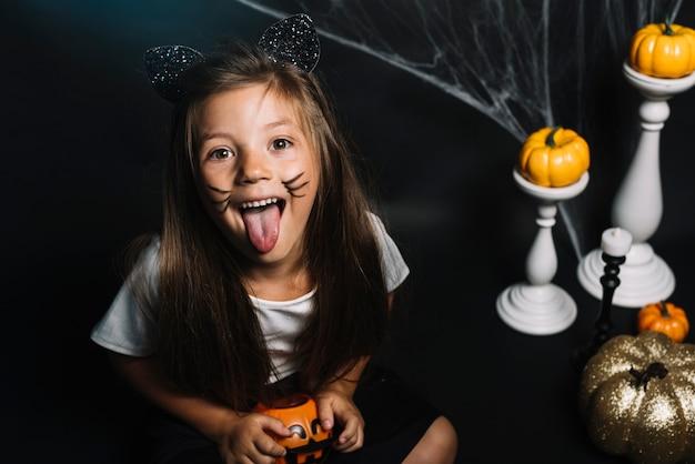 Chica en traje de gato mostrando la lengua