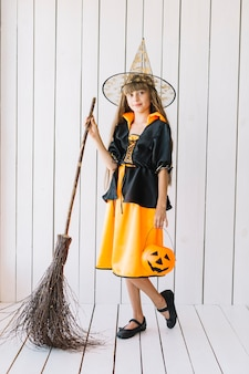 Chica en traje de halloween con escoba posando en estudio