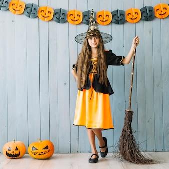Chica en traje de halloween de pie con escoba y calabazas