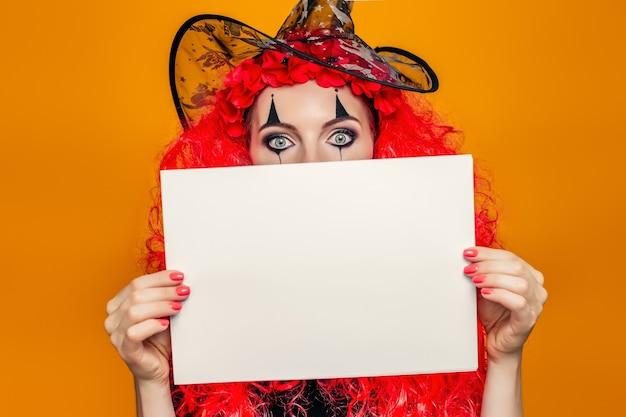 Chica en traje de halloween sosteniendo una hoja de papel.