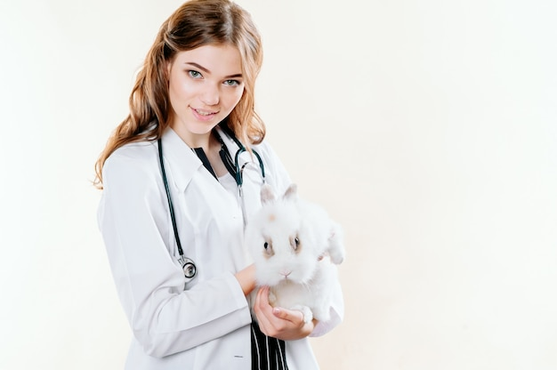 Chica en un traje de un médico veterinario con un conejo en sus manos