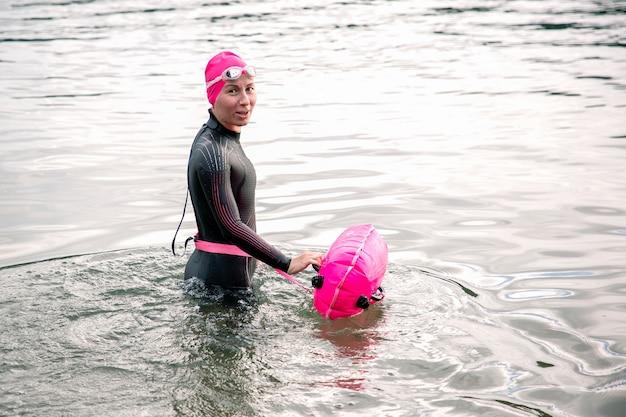 Chica en traje de neopreno posando en el agua