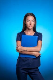 Chica en un traje quirúrgico azul posando de pie sobre un fondo azul abrazando una tableta azul para registros en sus manos y un bolígrafo. cuidado para las personas. medicina.