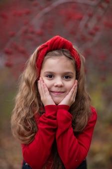 Chica en traje rojo en el bosque de otoño