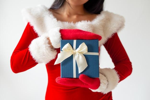 Chica en traje de santa mostrando caja de regalo