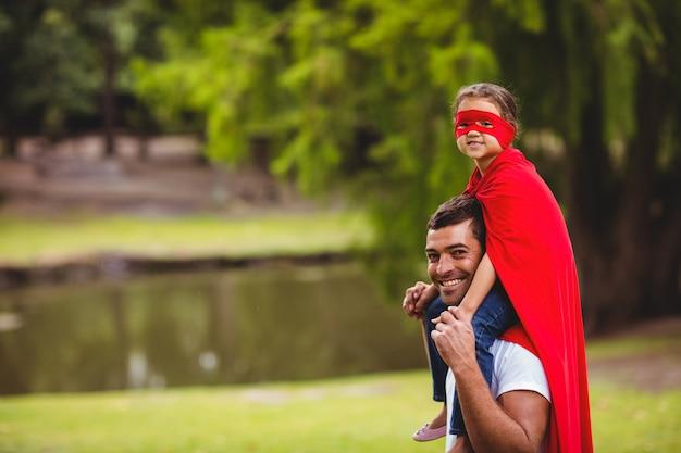 Chica en traje de superhéroe sentada en el hombro del padre
