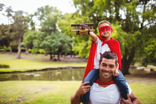 Chica en traje de superhéroe sentada sobre los hombros del padre