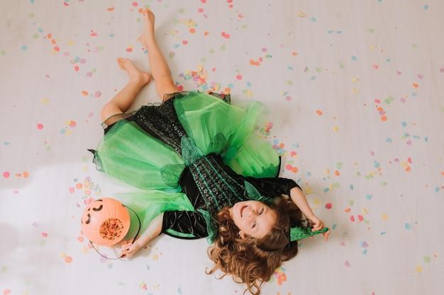 Chica en traje verde de halloween de una bruja o hada yace en el suelo sembrado de confeti de colores