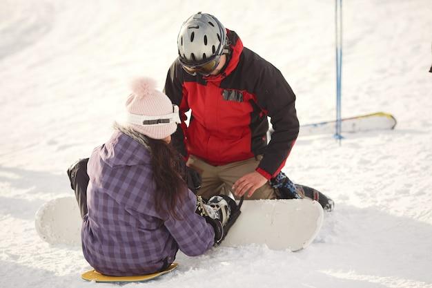 Chica tratando de subirse a una tabla de snowboard. guy le da una mano a la chica. traje morado.