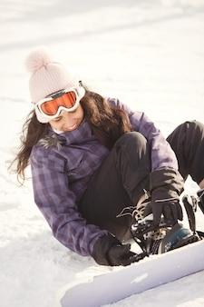 Chica tratando de subirse a una tabla de snowboard. mujer sentada sobre la nieve. traje morado.