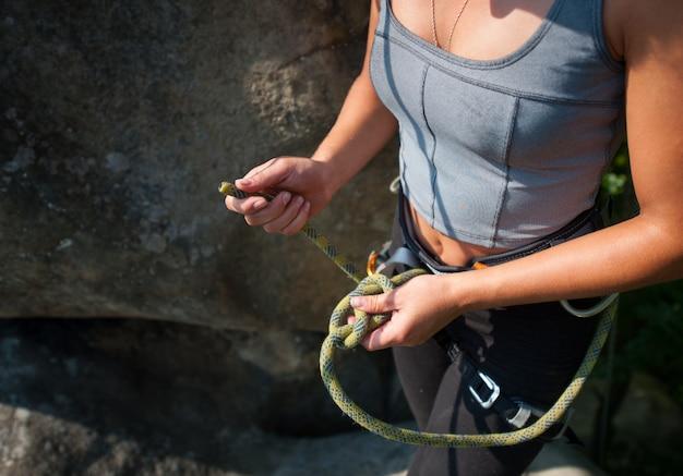 Chica trepadora con arnés de seguridad atando una cuerda en ocho nudos