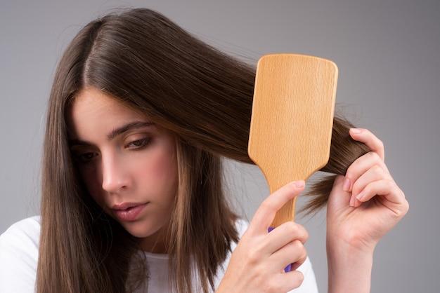 Chica triste con cabello dañado. tratamiento del problema de la caída del cabello. retrato de mujer con peine y cabello problemático.