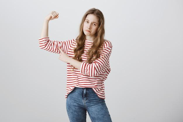 Chica triste flexiona los bíceps y se queja de lo débil que está